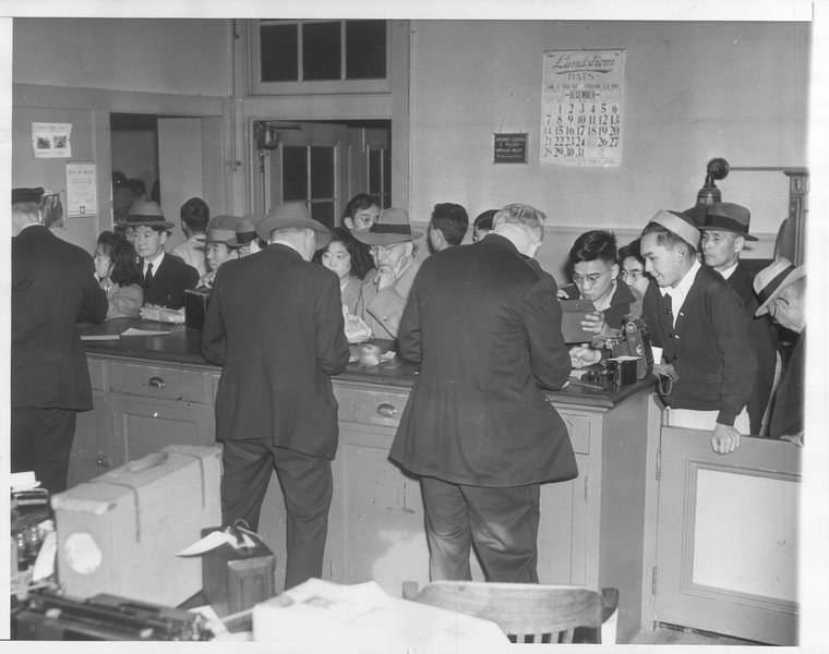 """""""West Coast aliens guive up cameras.  On order of the United States Department of Justice, alien Japanese, Germans and italians swarmed San Francisco police headquarters to surrender shortwave radios and all cameras.""""--caption on photograph"""