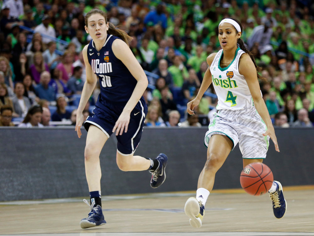 Description of . Notre Dame guard Skylar Diggins (4) drives against Connecticut forward Breanna Stewart (30) in the first half of the women\'s NCAA Final Four college basketball tournament semifinal, Sunday, April 7, 2013, in New Orleans. (AP Photo/Dave Martin)