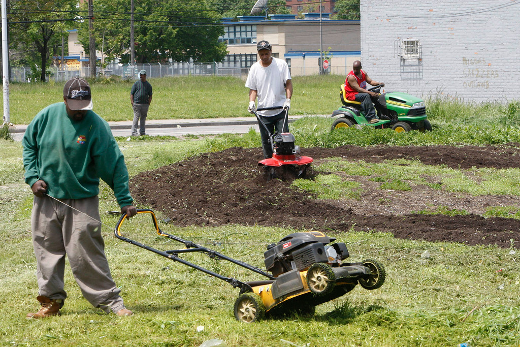 """. In this Thursday, May 20, 2010 photo, work crews clear out an empty lot in Detroit, . A nonprofit that puts vacant urban land to use for growing food will kick off work next week on one of several new community gardens it\'s planning for the Detroit area under a nationwide partnership with Kraft Foods Inc.\'s Triscuit brand. Next Thursday\'s planned groundbreaking is part of an effort that Detroit-based Urban Farming and Triscuit began in March to create about 50 \""""home farms\"""" in 20 areas around the U.S. from Los Angeles to Washington, D.C. (AP Photo/Carlos Osorio)"""