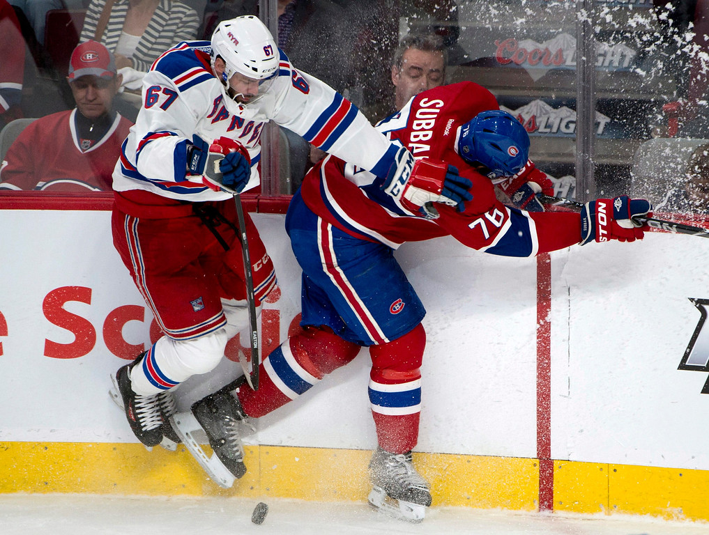 . New York Rangers left wing Benoit Pouliot, left, collides with Montreal Canadiens defenceman P.K. Subban along the boards during second period in Game 1 of the Eastern Conference finals in the NHL hockey Stanley Cup playoffs against in Montreal on Saturday, May 17, 2014. (AP Photo/The Canadian Press, Adrian Wyld)