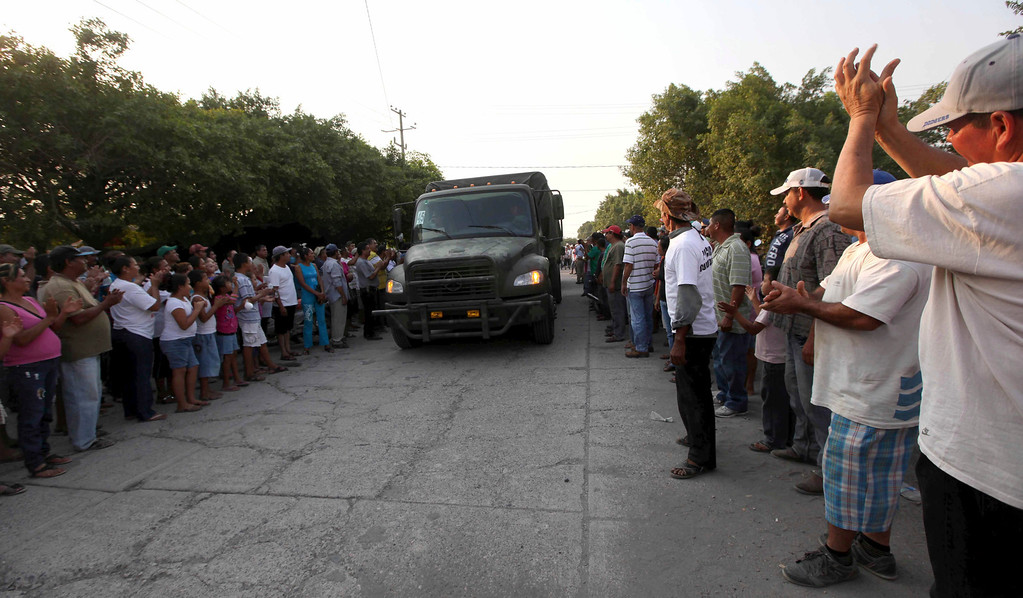 . In this May 20, 2013 photo, residents cheer as soldiers enter the town of La Ruana, Mexico. Self-defense groups started to spring up in February to fight back the Knights Templar drug cartel which is extorting protection payments from cattlemen and lime growers, butchers and even marijuana growers. Many of the vigilante squads disappeared this week with the arrival of the army, though they vow to take up arms again as soon as the soldiers leave.  (AP Photo/Marco Ugarte)