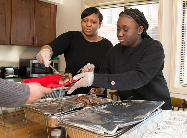 12/20/19 Wesley Bunnell | StaffrrMarie Sergeant, L, helps to serve melas along with senior Yhaaira Shaw at Howey House on Monday afternoon as part of a senior Capstone Project along with two other seniors. Howey House is a part of shelter for chronically homeless persons.