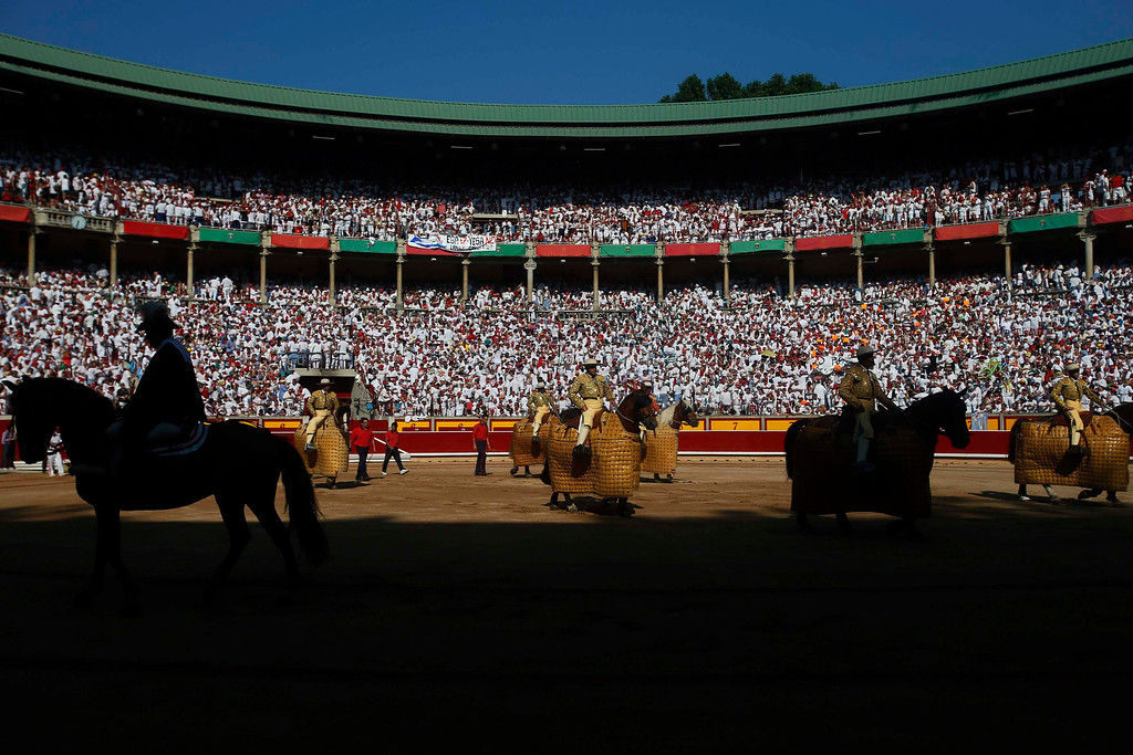 ". ""Picadores\"" (mounted bullfighters) enter the bull ring at the start of the fifth bullfight of the San Fermin festival in Pamplona July 11, 2013. REUTERS/Susana Vera"