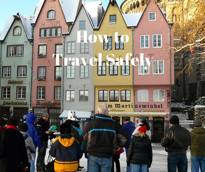 How to travel safely. Crowd listens to tour guide in front of colorful buildings.