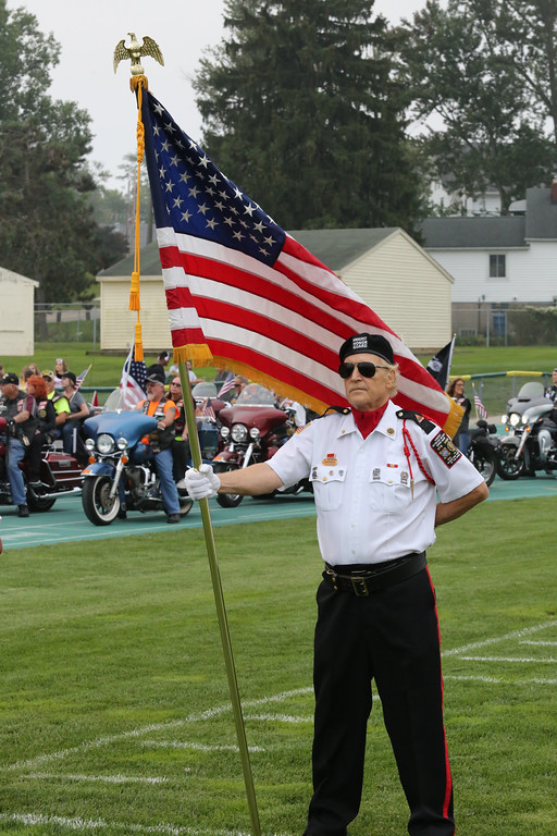 . David Schneider - The Morning Journal<br> Jeff Osko of the Amherst Honor Guard holds the flag as the American Legion Riders (background) prepare to circle the track before the game. They were all part of the POW-MIA seat dedication in the home bleachers.
