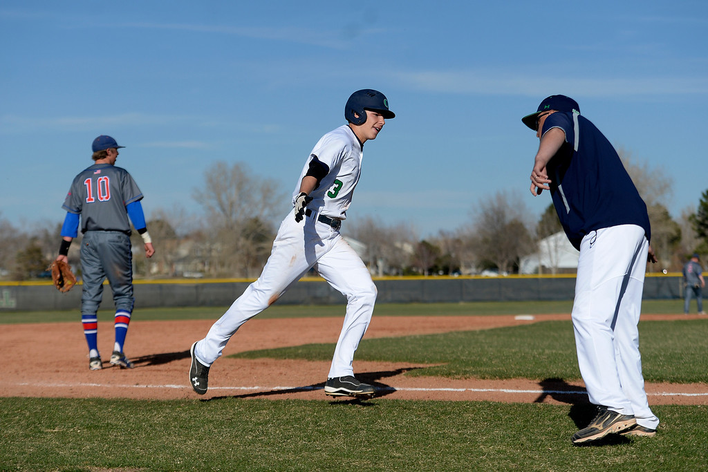 . Aurora, CO - APRIL 08: Overland Trailblazers high fives Joe Slocum (3) as he rounds third after hitting a three-run game-tying home run against the Cherry Creek Bruins during league action. Overland hosted Cherry Creek on Tuesday, April 8, 2014. (Photo by AAron Ontiveroz/The Denver Post)