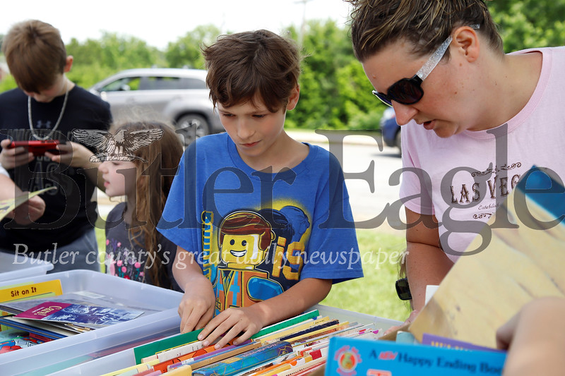 Xavier Oniboni, 10, and his mother Christina browse for books at the Butler School District book swap.