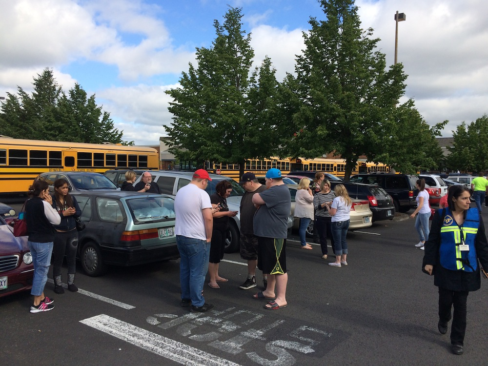 . People gather at Fred Meyer grocery store t in Wood Village, where they will be able to pick up their children after a school shooting at Reynolds High School in Troutdale, Ore., on Tuesday, June 10, 2014.   One student and the suspected gunman are dead in a school shooting outside Portland, Ore., according to the police.   The Multnomah County sheriff\'s office said there were reports of shots fired about 8 a.m. Students said they were told over the intercom there was a lockdown and to quietly go to their classrooms. (AP Photo/The Oregonian, Thomas Boyd)