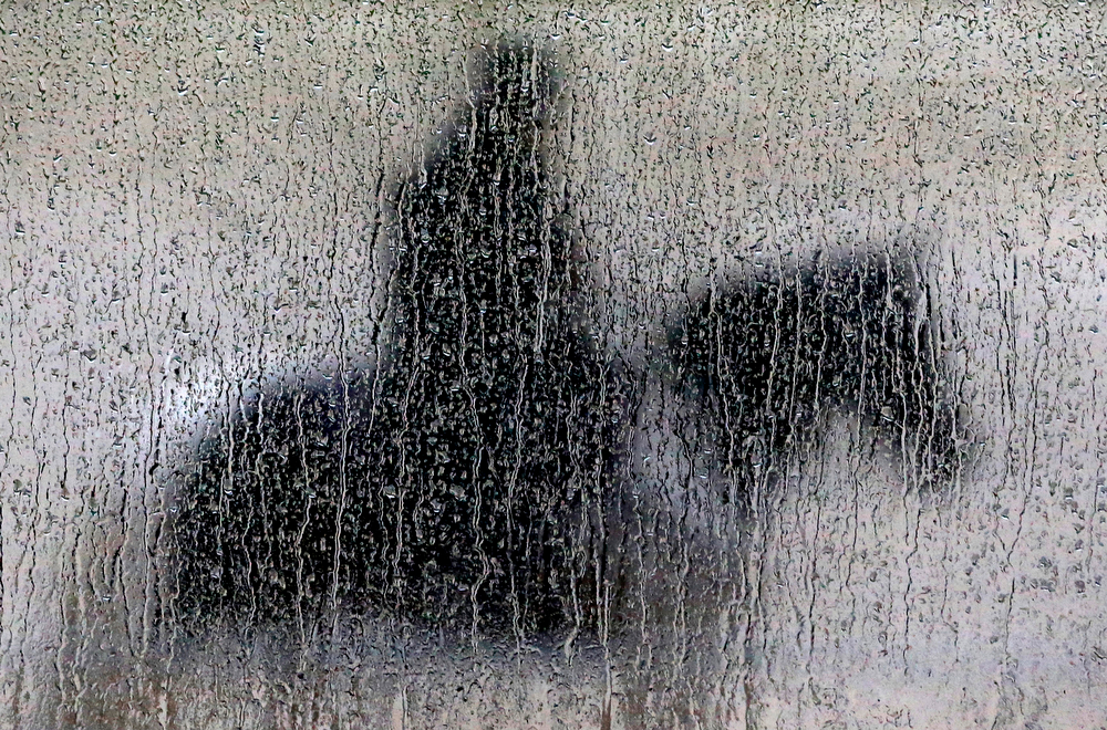 . Rain runs down a pane of glass as a woman aboard a pony waits to guide a horse off the track during a workout session at Pimlico Race Course in Baltimore, Friday, May 16, 2014. The Preakness Stakes horse race is scheduled to take place on Saturday, May 17. (AP Photo/Patrick Semansky)