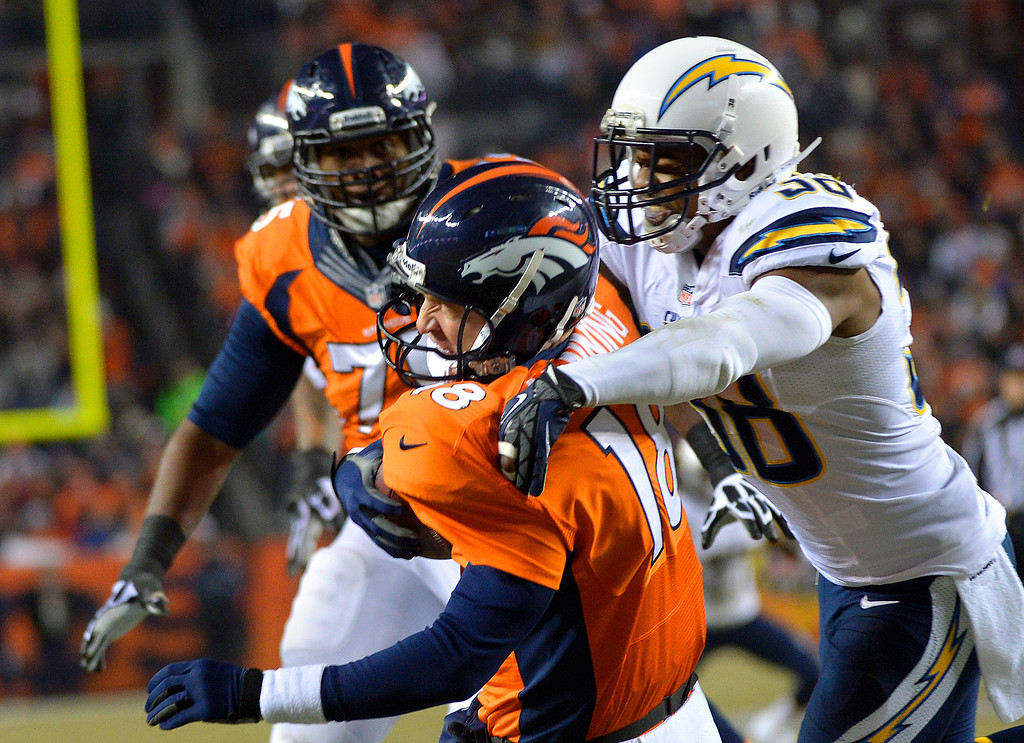 . Denver Broncos quarterback Peyton Manning (18) gets sacked by San Diego Chargers strong safety Marcus Gilchrist (38) during the second quarter. The Denver Broncos vs. the San Diego Chargers at Sports Authority Field at Mile High in Denver on December 12, 2013. (Photo by Joe Amon/The Denver Post)