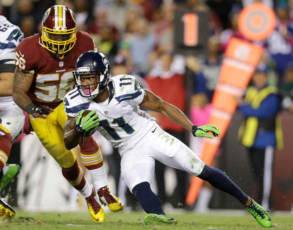 . Seattle Seahawks wide receiver Percy Harvin (11) carries the ball past Washington Redskins inside linebacker Perry Riley (56) during the first half of an NFL football game in Landover, Md., Monday, Oct. 6, 2014. (AP Photo/Patrick Semansky)
