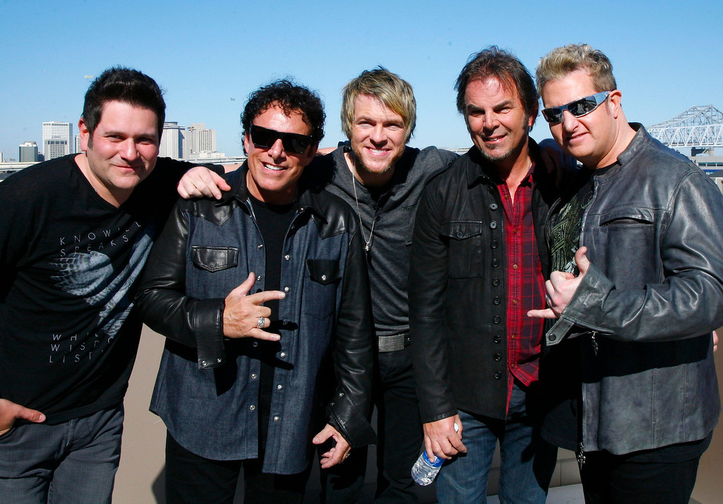. Journey\'s Jonathon Cain, left, and Neil Schon, second from left, pose with Rascal Flats Joe Dan Rooney, center, Jay DeMarcus and Gary Levox, right, in New Orleans Friday Feb. 1, 2013.  Journey and Rascal Flatts got on stage together for CMT\'s Crossroads concert Super Bowl weekend.  (AP Photo/ John Carucci)
