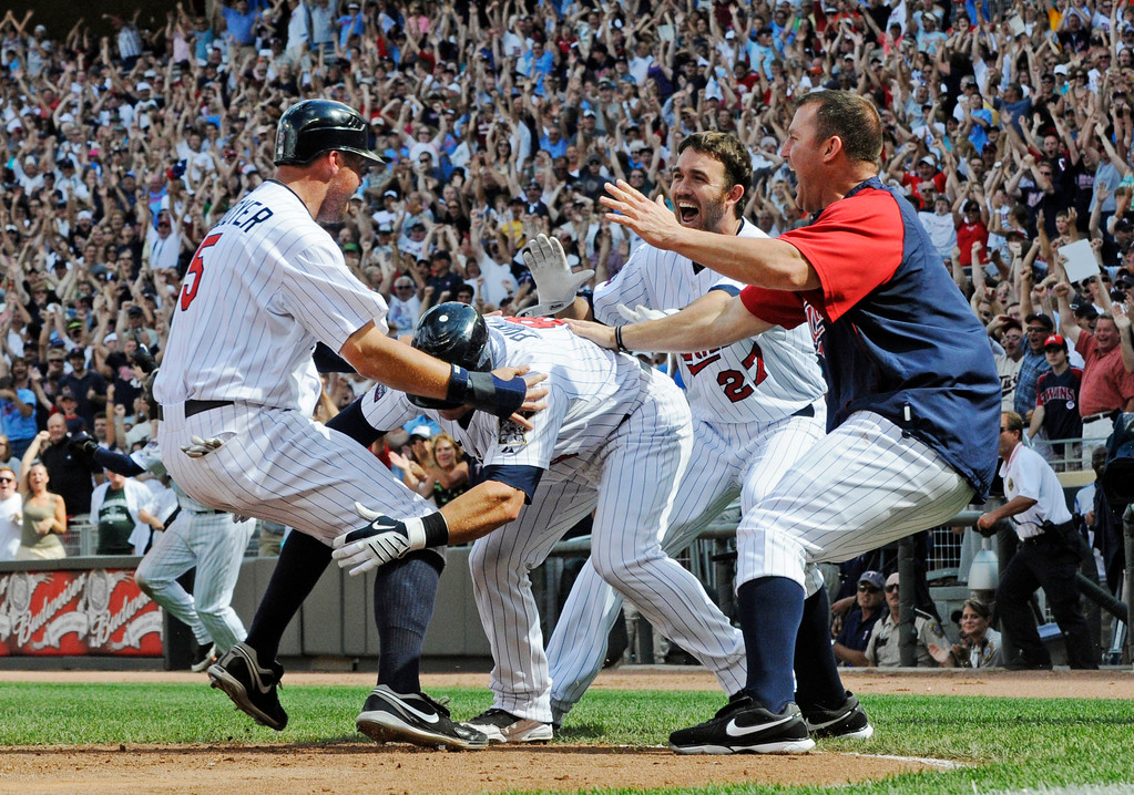 . Minnesota Twins\' Michael Cuddyer, left, is greeted by Nick Punto, J.J. Hardy (27) and Jim Thome, right, after he scored the winning run on a Delmon Young hit off Chicago White Sox pitcher Dergio Santos in the ninth inning of a baseball game Sunday, July 18, 2010 in Minneapolis. The Twins won 7-6. (AP Photo/Jim Mone)