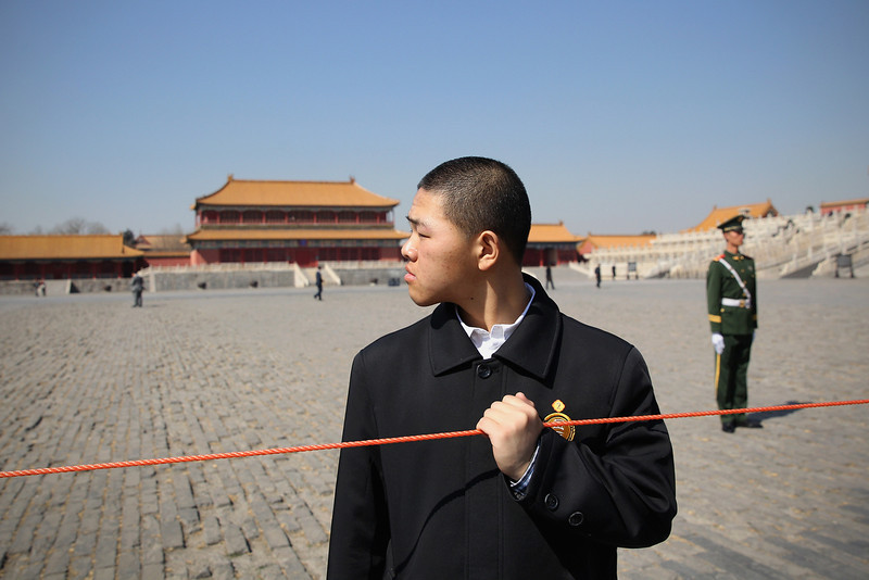 . A Chinese security officer holds a police line rope during U.S. First Lady Michelle Obama\'s visit to the Forbidden City on March 21, 2014 in Beijing, China. Michelle Obama\'s one-week-long visit in China will be focused on educational and cultural exchanges.  (Photo by Feng Li/Getty Images)