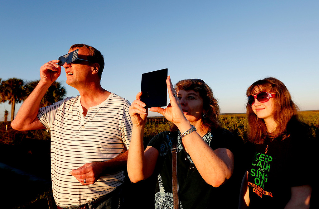 . Andy, Cathy and Jessica Howell look at a partial eclipse of the sun on Thursday, Oct. 23, 2014 in Gainesville, Fla. (AP Photo/The Gainesville Sun, Matt Stamey)