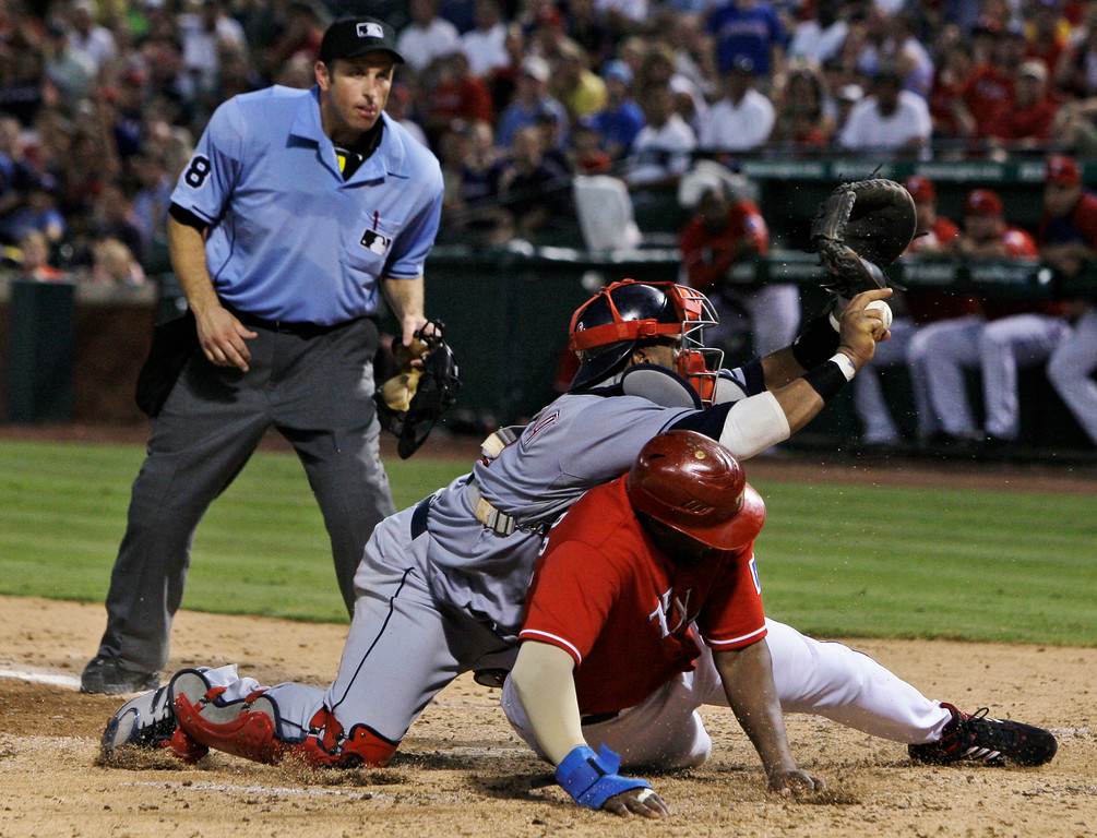 . Home plate umpire Chris Guccione watches as Cleveland Indians catcher Carlos Santana holds on to the ball following a collision at the plate with Texas Rangers\' Vladimir Guerrero in the fifth inning of a baseball game Tuesday, July 6, 2010, in Arlington, Texas. Guerrero was trying to score on a single by Nelson Cruz. (AP Photo/Tony Gutierrez)