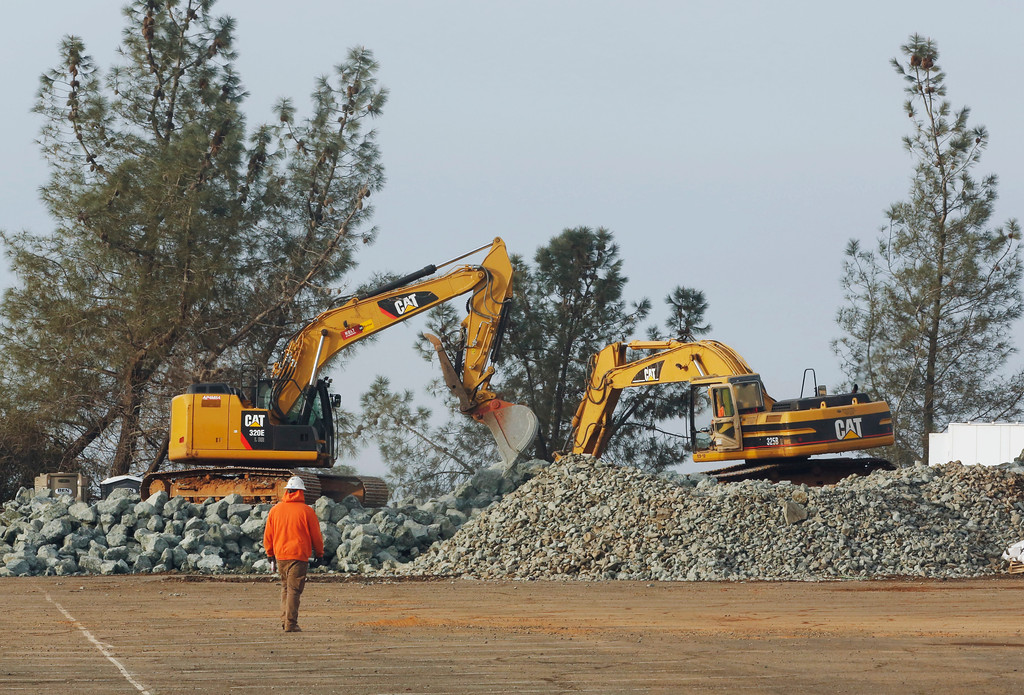 . Construction equipment moves piles of rock at a staging area near the Oroville Dam, Monday, Feb. 13, 2017, in Oroville, Calif. State officials have discussed using helicopters to drop loads of rock on the damaged emergency spillway of the dam. (AP Photo/Rich Pedroncelli)