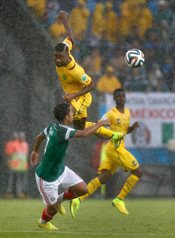 . Cameroon\'s Cedric Djeugoue leaps to win a header during the group A World Cup soccer match between Mexico and Cameroon in the Arena das Dunas in Natal, Brazil, Friday, June 13, 2014.  (AP Photo/Sergei Grits)