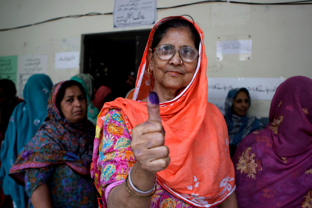 . A Pakistani woman shows her ink-stained thumb after casting her ballot at a polling station in Lahore, Pakistan, Saturday, May 11, 2013. Defying the danger of militant attacks, Pakistanis streamed to the polls Saturday for a historic vote pitting a former cricket star against a two-time prime minister and an unpopular incumbent. But bombings that killed and wounded dozens underlined the risks many people took just casting their ballots. (AP Photo/K.M. Chaudary)