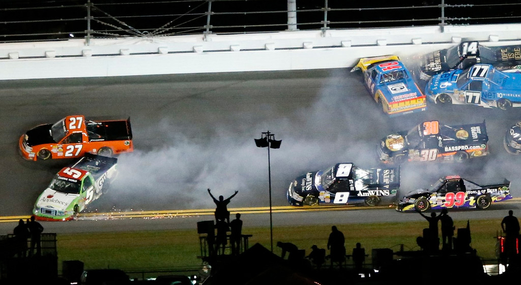 . Fans react as trucks crash in front of them during the NASCAR Camping World Truck Series NextEra Energy Resources 250 race at the Daytona International Speedway in Daytona Beach, Florida February 22, 2013. Crashing at left are Jeff Agnew in his number 27 Chevrolet and Tim George Jr. in his number 5 Ford. The Daytona 500 NASCAR Sprint Cup race is scheduled for February 24. REUTERS/Pierre Ducharme