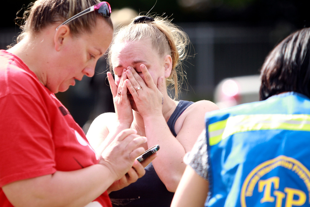 . A person wipes away tears as they await to hear about the safety of students after a shooting at Reynolds High School Tuesday, June 10, 2014, in Troutdale, Ore. A gunman killed a student at the high school east of Portland Tuesday and the shooter is also dead, police said. (AP Photo/The Oregonian, Faith Cathcart)