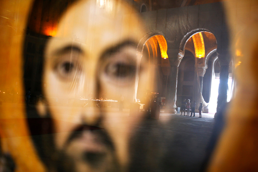 . Worshippers, reflected on a glass case of an icon of Christ, pray during Good Friday at the St. Sava temple in Belgrade May 3, 2013. Serbia and other Eastern Orthodox countries celebrate Easter this weekend.  REUTERS/Marko Djurica