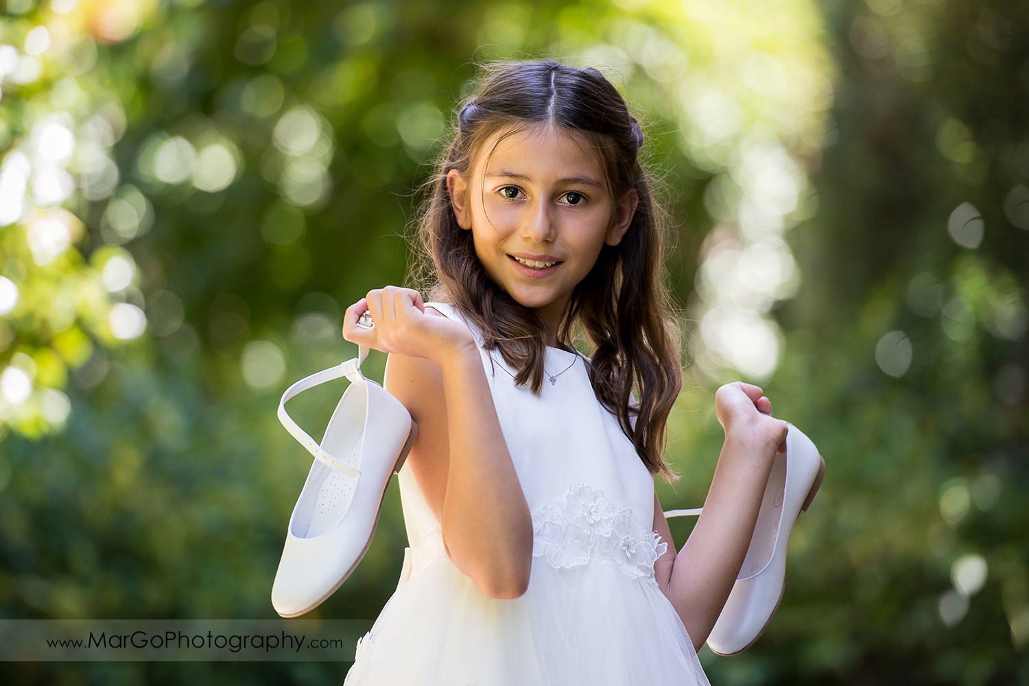 portrait of first communion girl in white dress holding white shoes at green background at Cafe Wisteria in Menlo Park