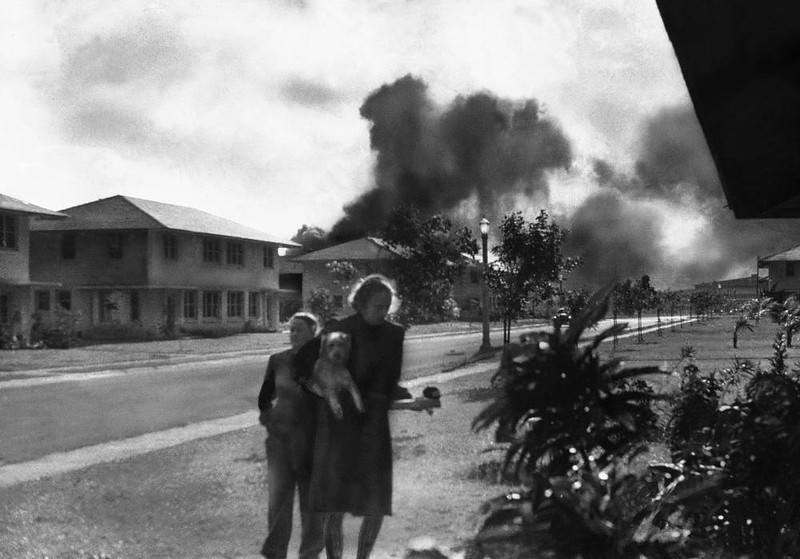 ". Officers\' wives, investigating explosion and seeing smoke pall in distance on Dec. 7, 1941, heard neighbor Mary Naiden, then an Army hostess who took this picture, exclaim ""There are red circles on those planes overhead. They are Japanese!\"" Realizing war had come, the two women, stunned, start toward quarters. (AP Photo/Mary Naiden)"
