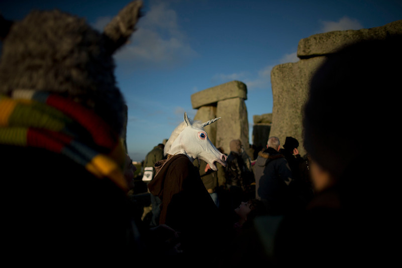 """. A person wears a unicorn mask after sunrise by the ancient stone circle of Stonehenge, in southern England, as access to the site is given to druids, New Age followers and members of the public on the annual Winter Solstice, Friday, Dec. 21, 2012.  Doomsday hour is here and so still are we.  According to legend, the ancient Mayans\' long-count calendar ends at midnight Thursday, ushering in the end of the world. Didn\'t happen.  \""""This is not the end of the world. This is the beginning of the new world,\"""" Star Johnsen-Moser, an American seer, said at a gathering of hundreds of spiritualists at a convention center in the Yucatan city of Merida, an hour and a half from the Mayan ruins at Chichen Itza. (AP Photo/Matt Dunham)"""