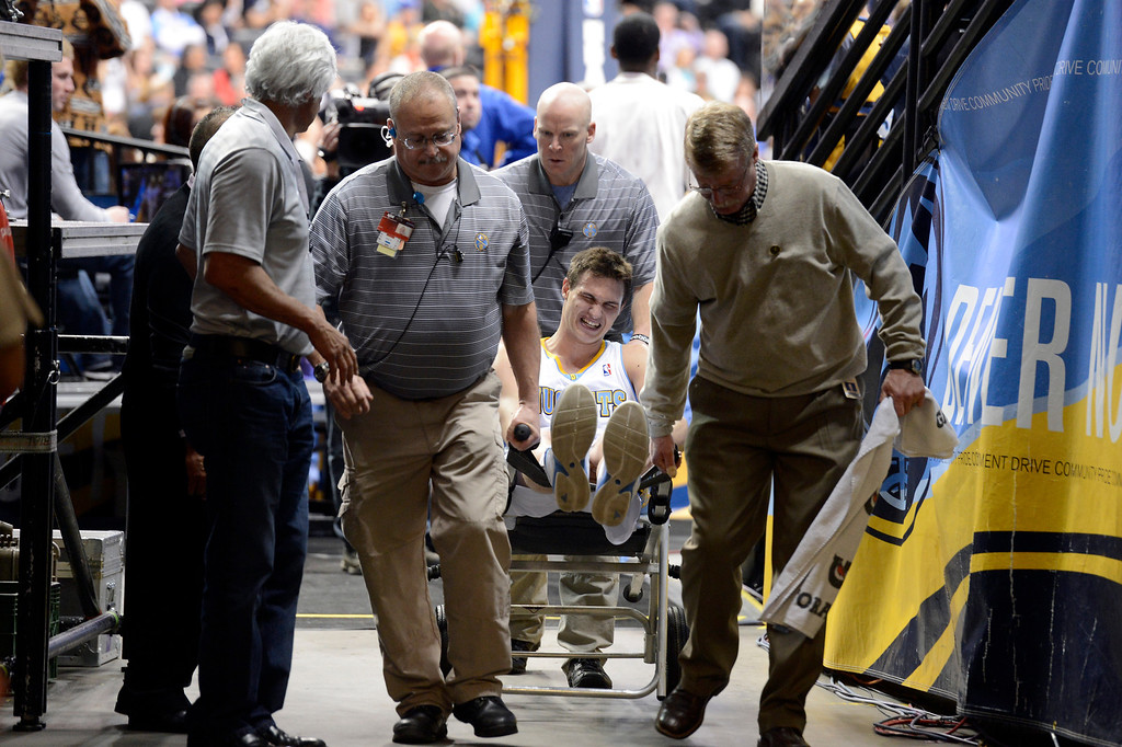 . DENVER, CO. - APRIL 04: Danilo Gallinari (8) of the Denver Nuggets is helped off the court after suffering a knee injury in second quarter April 4,  2013 against the Dallas Mavericks at Pepsi Center. (Photo By John Leyba/The Denver Post)