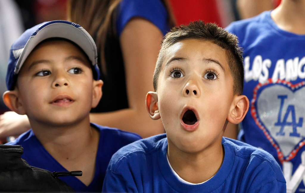 . Los Angeles Dodgers fans watch a ball clear the fence during batting practice before a baseball game against the Arizona Diamondbacks, Wednesday, Sept. 18, 2013, in Phoenix. (AP Photo/Ross D. Franklin)