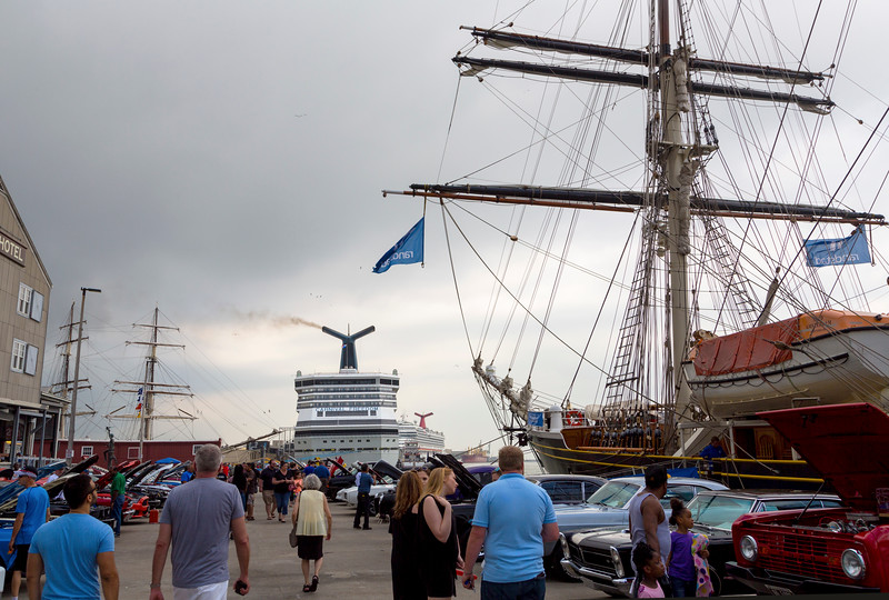 Four ships, 1 old, 2 new, and 1 replica, surrounded by cars.