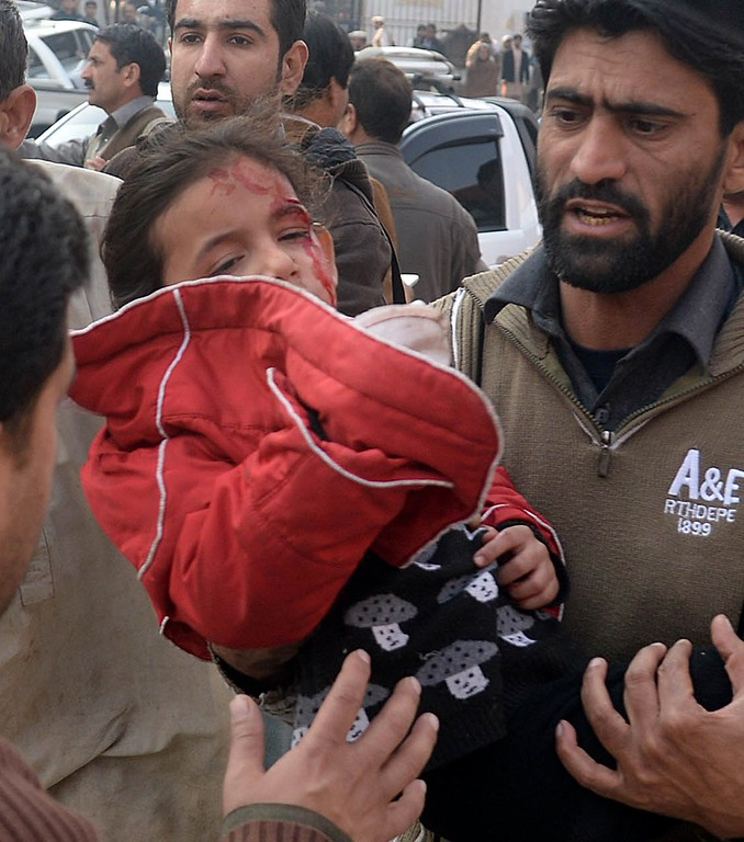 . Pakistani men carry an injured school girl to a hospital following an attack by Taliban gunmen on a school in Peshawar on December 16, 2014.  At least 130 people were killed in a Taliban attack on an army-run school in northwest Pakistan, officials said. AFP PHOTO/ A  Majeed/AFP/Getty Images