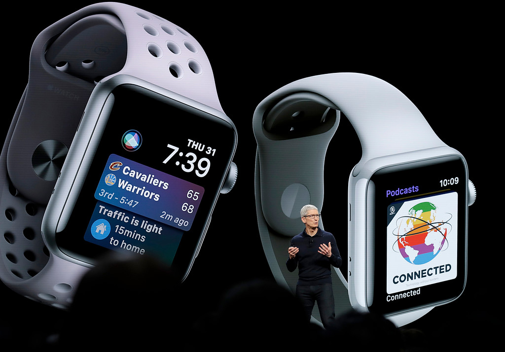 . Apple CEO Tim Cook speaks in front of images of the Apple Watch during an announcement of new products at the Apple Worldwide Developers Conference Monday, June 4, 2018, in San Jose, Calif. (AP Photo/Marcio Jose Sanchez)