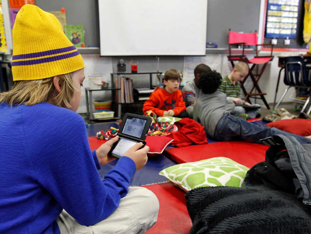 . Gavin Chambers plays an electronic game at Oak Mountain Intermediate school on Wednesday, Jan. 29, 2014, in Indian Springs, Ala. About 80 children  and 20 adults spent the night at the school due to a winter storm.  Overnight, the South saw fatal crashes and hundreds of fender-benders. Jackknifed 18-wheelers littered Interstate 65 in central Alabama. (AP Photo/Butch Dill)