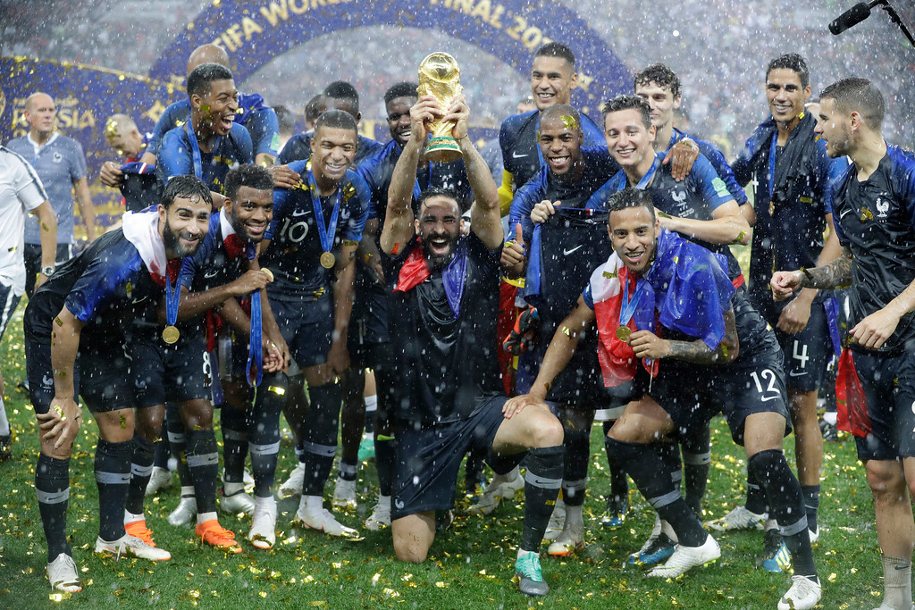 . France\'s Adil Rami, center, celebrates with the trophy after the final match between France and Croatia at the 2018 soccer World Cup in the Luzhniki Stadium in Moscow, Russia, Sunday, July 15, 2018. France won the final 4-2. (AP Photo/Matthias Schrader)