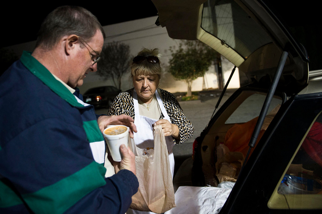 . Nicolette Wingert and Phillip Stern grab meals from the car to distribute to the homeless people in Covina on Wednesday night, Nov. 27, 2013. Nicolette Wingert has been feeding the homeless six days a week for the past seven years with Nurses4Christ, a nonprofit organization she founded in 2006. She and Phillip Stern of Glendora have been going every day since 2008, feeding homeless people sandwiches and hot food; giving them bottles of water, clothes and blankets. (Photo by Watchara Phomicinda/San Gabriel Valley Tribune)