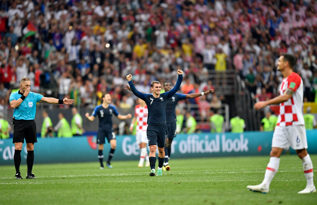 . France\'s Antoine Griezmann, center, celebrates winning the World Cup as referee Nestor Pitana from Argentina, left, blows the final whistle during the final match between France and Croatia at the 2018 soccer World Cup in the Luzhniki Stadium in Moscow, Russia, Sunday, July 15, 2018. (AP Photo/Martin Meissner)