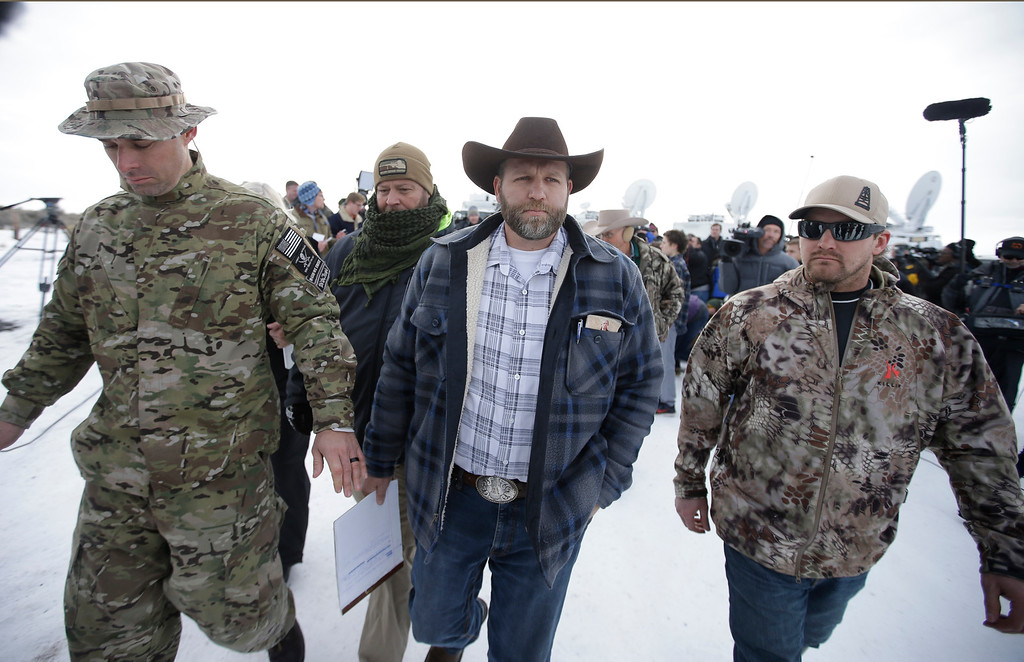 . Ammon Bundy, center, one of the sons of Nevada rancher Cliven Bundy, walks off after speaking with reporters during a news conference at Malheur National Wildlife Refuge headquarters Monday, Jan. 4, 2016, near Burns, Ore. Bundy, who was involved in a 2014 standoff with the government over grazing rights told reporters on Monday that two local ranchers who face long prison sentences for setting fire to land have been treated unfairly. (AP Photo/Rick Bowmer)