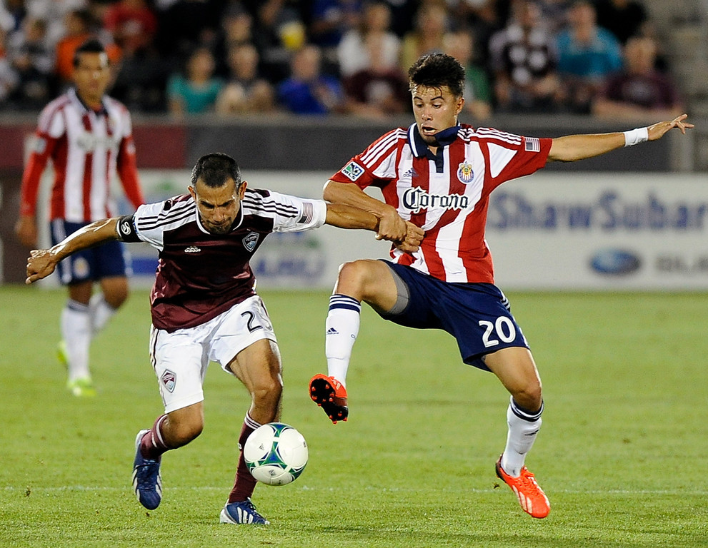 . Colorado Rapids midfielder Pablo Mastroeni, left, of Argentina, fights for the ball against Chivas USA midfielder Carlos Alvarez, right, in the second half of an MLS soccer game in Commerce City, Colo., on Saturday, May, 25 2013. The Rapids won 2-0. (AP Photo/Chris Schneider)