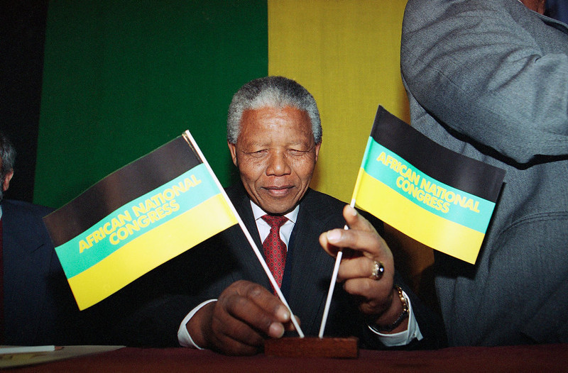 . Nelson Mandela, President of the African National Congress, adjusts his party\'s flags before the start of his press conference on Tuesday, May 4, 1993 in London hotel.   Mandela, in Britain as the guest of the British government, said the greatest threat to peace in South Africa is from white rightwing extremists. (AP Photo/Denis Paquin)