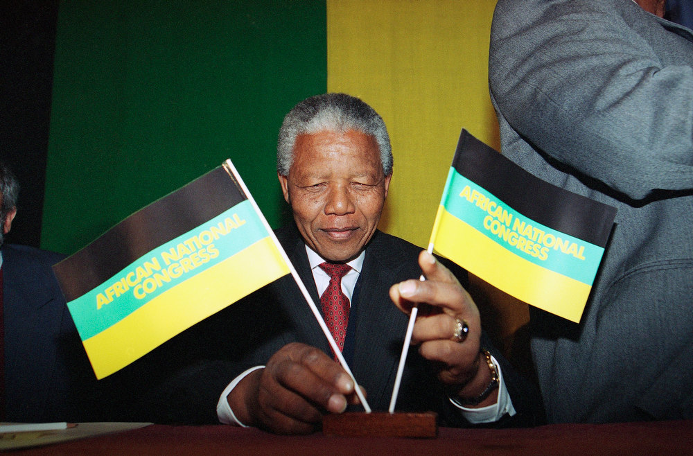 Description of . Nelson Mandela, President of the African National Congress, adjusts his party's flags before the start of his press conference on Tuesday, May 4, 1993 in London hotel.   Mandela, in Britain as the guest of the British government, said the greatest threat to peace in South Africa is from white rightwing extremists. (AP Photo/Denis Paquin)