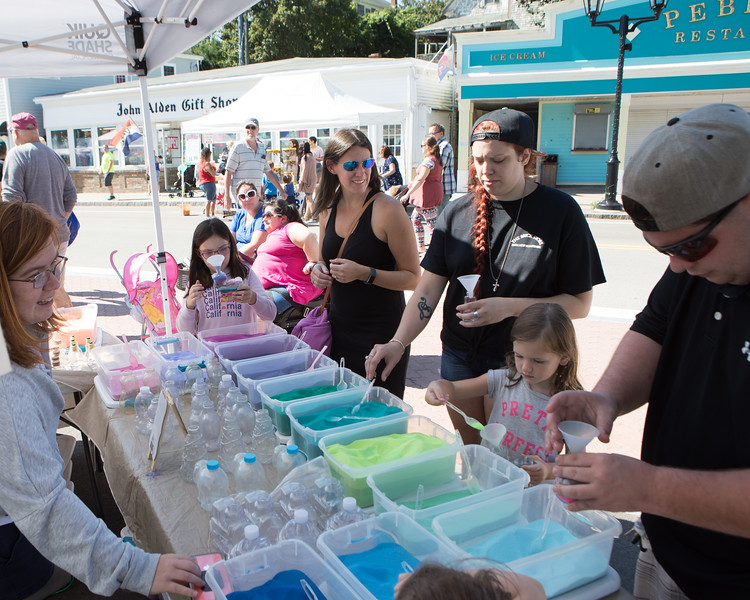 Children and their parents are having fun filling bottles of all shapes with colored sand at the Sand Art booth.  [Wicked Local Photo/Denise Maccaferri]