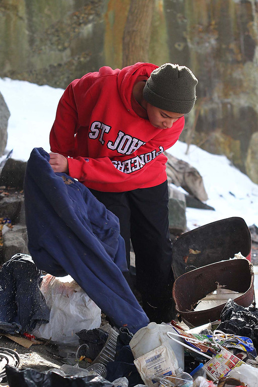. Jeremy Lundin, 14, the cousin to Jeremiah Oliver\'s half brothers, searches in the trash under the Rollstone street bride for Jeremiah who has not been sen since Sept. 14, 2013 during a search on Saturday in Fitchburg. SENTINEL & ENTERPRISE/JOHN LOVE