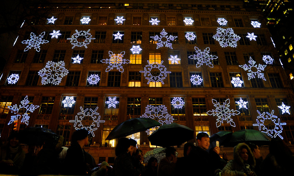 . Onlookers pass by Saks Fifth Ave. before the 77th annual Rockefeller Center Christmas tree lighting ceremony Wednesday, Dec. 2, 2009 in New York. (AP Photo/Stephen Chernin)