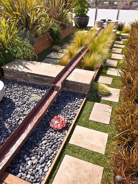 Contemporary loft outdoor space design with stone pathway and water feature.