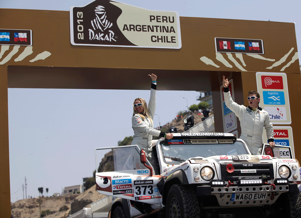 . Driver Anthony Harris, of Great Britain, right, and his co-driver Catherine Derousseaux, of France, wave from the podium ramp during the symbolic start of the Peru-Argentina-Chile Dakar Rally 2013 in Lima, Peru, Saturday, Jan. 5, 2013. The race of over 400 vehicles including cars, bikes, trucks and quads begins Saturday in Lima, and finishes in Santiago, Chile on Jan. 20. (AP Photo/Martin Mejia)