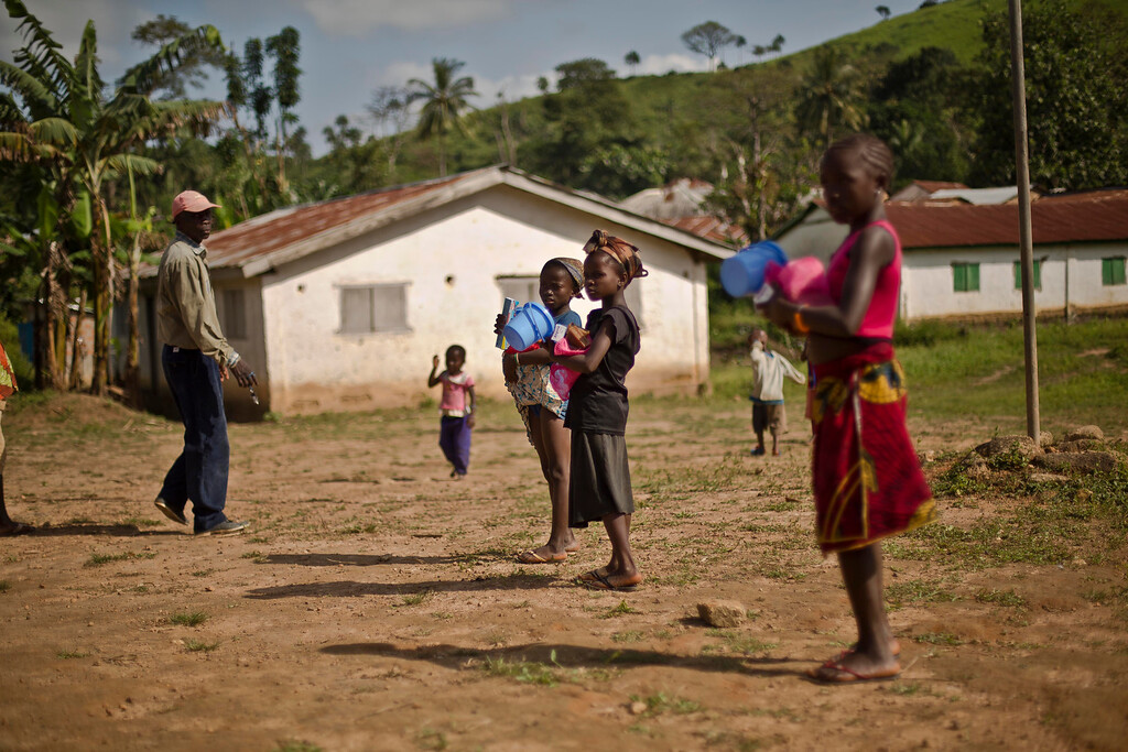 . In this photo taken Thursday Nov. 20, 2014, children carry sanitization kits supplied by UNICEF  in the Guinean village of Meliandou, some 400 miles (600 kms) south-east of Conakry, Guinea, believed to be Ebola\'s ground zero. I(AP Photo/Jerome Delay)