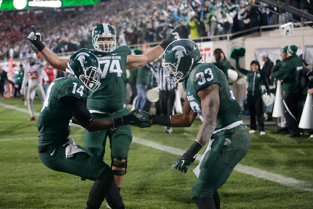 . Michigan State running back Jeremy Langford (33) celebrates with wide receiver Tony Lippett (14) and offensive tackle Jack Conklin (74) after his a 33-yard touchdown run against Ohio State during the first half of an NCAA college football game in East Lansing, Mich., Saturday, Nov. 8, 2014. (AP Photo/Carlos Osorio)
