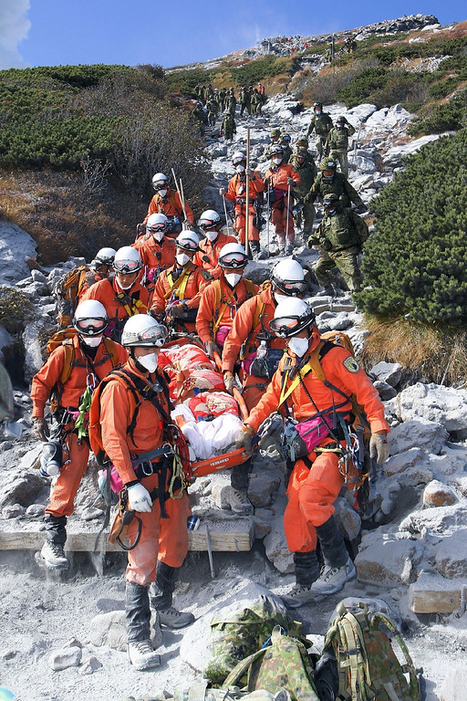 . This handout picture taken by the Tokyo Fire Department on September 28, 2014 and released on September 30 shows firefighters carrying an injured climber down from Mount Ontake in Nagano prefecture, one day after the volcano erupted. The grim discovery takes to at least 36 the total number of people feared to have died when Mount Ontake erupted without warning during a busy hiking weekend.   AFP PHOTO / TOKYO FIRE DEPARTMENT via JIJI PRESS/AFP/Getty Images